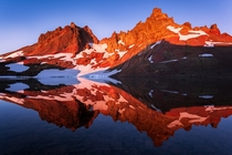 First light hitting Broken Top Mountain in central Oregon providing an incredible glow and reflection on its glacial lake