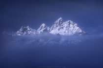 Float On Teton Range Glowing Through Fog on a Moonlit Winter Night  by Alex Noriega