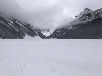 Fog rolling in over a frozen solid Lake Louise - Alberta Canada