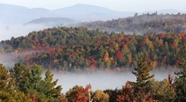 Fog sits in the valley of the White Mountains as leaves change colors Milan Hill NH  Photo by Jim Cole