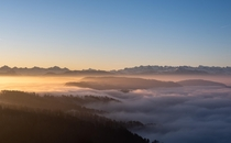 Fog slowly flowing over a chain of hills shortly after sunrise Zurich Switzerland