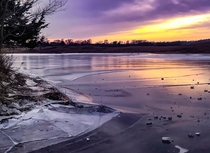 Frozen pond on an American prairie at sunset