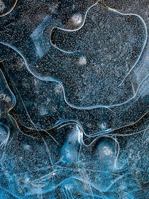 Frozen puddle of water with ice patterns and vibrant blue colour