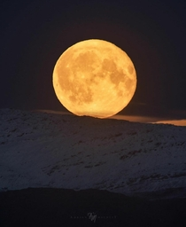 Full Hunters Moon rise above the snow-capped mountains of Senja in Norway