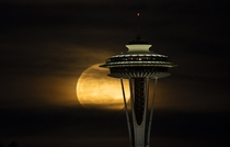 Full moon rising behind space needle in Seattle