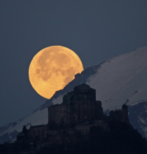 Full moon setting behind Sacra di San Michele