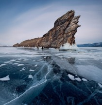 Giant rock surrounded by cracked ice of Lake Baikal Siberia