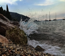 Glass-like wave after crushing into rocks on Garda Lake northern Italy