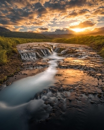 Golden light illuminating a waterfall in Iceland  IG holysht
