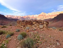 Grand Canyon Arizona Native American watchtower with sun on canyon in the background