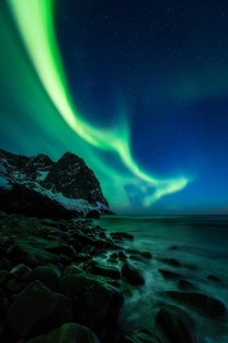 Green flames on the blue vernal night sky and grumbled pieces of the mighty mountains pounded and shaped by the endless great open ocean waves Lofoten Norway   mpxmark
