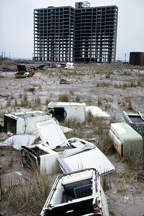 Greetings from New York  style Skeleton of apartment building never completed abandoned refrigerators and a burned out  Ford Mustang Breezy Point Queens looking toward Brooklyn New York Photo by Andy Blair