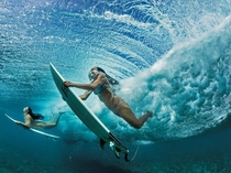 Haa Keaulana and Maili Makana dive under a wave on their way to surf near Makaha on Oahu Hawaii