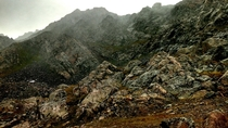 Hail and fog blowing against a two-thousand foot band of broken cliffs in Colorados gnarliest mountain range