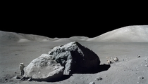 Harrison H Schmitt photographed standing next to a huge split lunar boulder during the third Apollo  extravehicular activity EVA at the Taurus-Littrow landing site