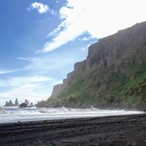 Hauntingly beautiful views of of a black sand beach hitting lush green cliffs in Vik Iceland