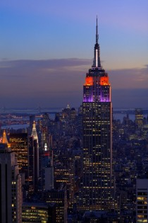 Heres the Empire State Building lit up in purple and orange with lower Manhattan in the background