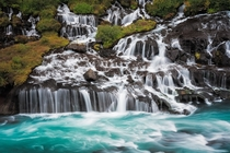 Hraunfossar Borgarfjrur western Iceland is a series of waterfalls formed by rivulets streaming over a distance of about  metres out of the Hallmundarhraun a lava field which flowed from an eruption of one of the volcanoes lying under the glacier Langjkull