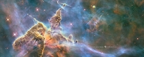 Hubbles th anniversary image shows a mountain of dust and gas rising in the Carina Nebula The top of a three-light-year tall pillar of cool hydrogen is being worn away by the radiation of nearby stars while stars within the pillar unleash jets of gas that