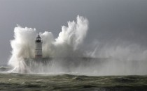 Huge waves break over the lighthouse on Newhaven Harbour as the country braces itself for more gales and rain Newhaven East Sussex England