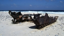 Hull of an Amtrac an armoured amphibious transport probably an LVT- rusting on a tropical beach