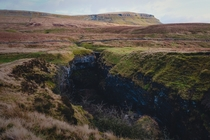 Hull Pot what remains of a cave with a collapsed roof with Pen-y-ghent looming in the distance Hull Pot Yorkshire Dales England