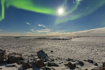 I bring you a very rare pic This is Nunavuts landscape in winter lit by the moon and northern lights above Nunavut Canada