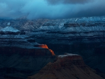 I hiked along the rim awaiting the arrival of the sun The skies were still overcast but a small break in the clouds allowed a single ray of sunlight to shine through illuminating a small portion of the butte below - Grand Canyon National Park Arizona  Pho