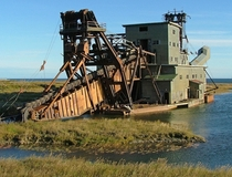 I saw a few abandoned dredgers in Alaska but this was the biggest by far located just outside of Nome near-arctic Alaska  The tail boom is also massive though its not clear from this angle Each scoop on the belt is the size of an arm chair The interior wa