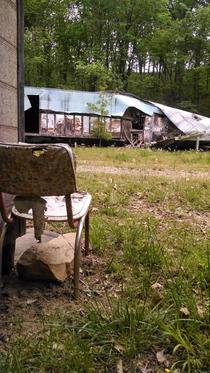 I saw this chair facing the the destroyed trailer home across from it and imagined what the slow demise of these homes looked like from the chairs perspective From a small abandoned town deep in the woods Eastern Kansas