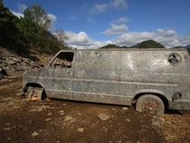 I waded through several inches of mud in order to photograph this beauty Typically submerged by Chilhowee Lake this van is visible when the lake is drained I climbed up on the hood and peeked through the windows discovering the interior was filled with we