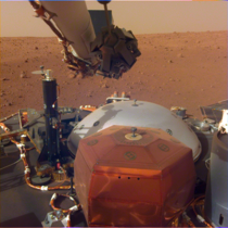 Image from InSights robotic-arm mounted Instrument Deployment Camera shows the instruments on the spacecrafts deck with the Martian surface of Elysium Planitia in the background