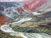 In the northern slopes of the Tian Shan Mountains in China a river carves its way through a canyon The layers are eroded by wind and water transforming the landscape into these colorful terraces  Photo by Tugo Cheng