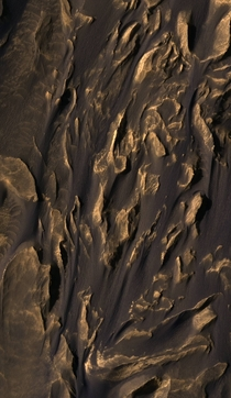 In this image SETI Institutes Lori Fenton explains that wind has blown the dark rippled sand between jagged Martian hills from top to bottom in this frame m or ft across