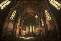 Inside the debris-strewn hall of an abandoned church  By DARKstyle Pictures