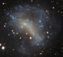 Irregular galaxy IC  roughly  million light-years away with milky way stars and galaxies blazing brightly in front of and behind respectfully making for a wonderful snapshot of the universe image credit Hubble
