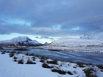 It snowed on our road trip last month and the loch was completely frozen over - Knockan Crag National Nature Reserve Scotland