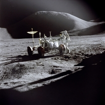 James Irwin works at the Lunar Roving Vehicle during the first Apollo  lunar surface EVA at the Hadley-Apennine landing site This view is looking northeast with Mons Hadley which has a height of  km and a maximum diameter of  km at its base in the backgro