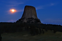 Jupiter Saturn and the full moon rising over Devils Tower Wyoming USA