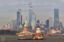 Lady Liberty and Robbins Reef lighthouse in front of Hudson Yards NYC