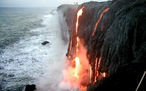 Lava falling in the ocean from a cliff in Hawaii