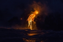Lava lights up the ocean waters in the darkness at Hawaiis G volcano flow