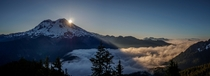 Light breaks from behind Mount Rainier and shines down on a sea of clouds -