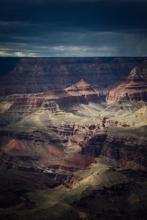 Light shining through heavy storm clouds onto the Grand Canyon