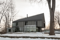 Limestone concrete and wood all work together to integrate the house to the natural tones of the site along the shores Lake Saint-Louis Lry Canada by Chevalier Morales