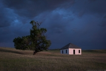 Little house on the prairie illuminated by lightning in rural Nebraska