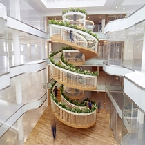 Living Staircase a living spiral staircase with open spaces for reading drawing relaxing and drinking tea forming the centrepiece of a newly created workspace in Soho London United Kingdom