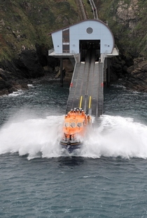 Lizard Lifeboat Station launches its lifeboat Rose into the waters of Kilcobben Cove England