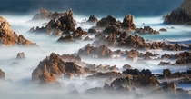 Long exposure of a rocky coast almost looks like an epic range of mountains in fog Haesindang Korea