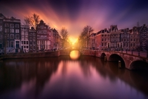 Long-exposure of the setting sun over the canals of Amsterdam  by Ivn Maigua